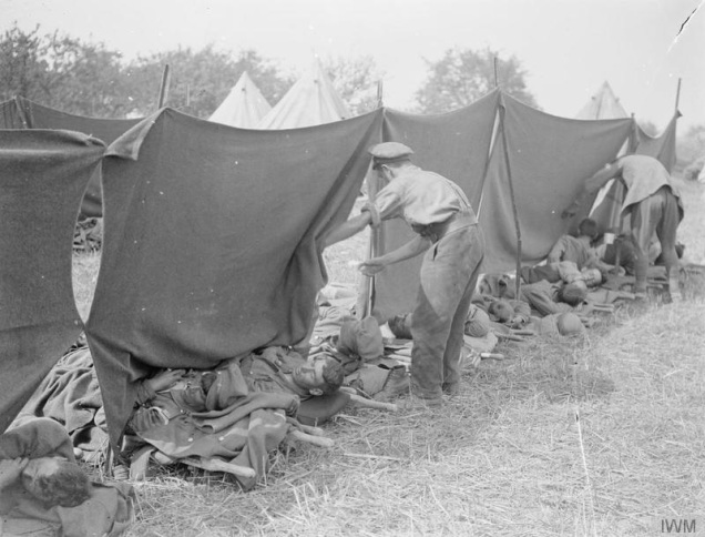 © IWM (Q 7299) Battle of Amiens. Arranging blankets to shade from the sun wounded awaiting evacuation from a Field Dressing Station at Le Quesnel, 11 August 1918